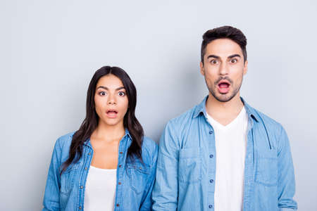 Photo pour It's unbelievable! Portrait of two shocked and surprised people dressed in denim clothing. They are standing with open mouths because they won a prize, isolated on grey background - image libre de droit