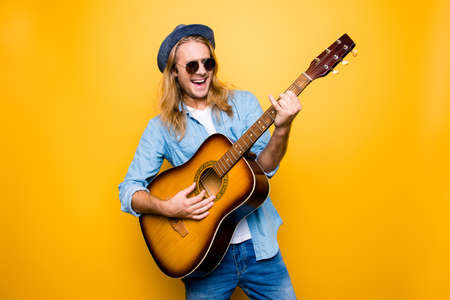 Photo for Music is my lifestyle! Excited and carefree musician dressed in casual clothes and spectacles playing the acoustic guitar and singing a song - Royalty Free Image