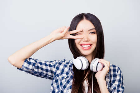 Foto de Beautiful relaxed asian girl with dark long hair, toothy smile is giving a wink, showing v-sign and listening to her favourite song, isolated on grey background - Imagen libre de derechos