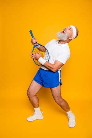 Photo for Full length of sexy emotional cool pensioner grandpa practising rock music on a  sport equipment, stands in pose, yell and shout. Body care, hobby, weight loss, lifestyle, strength and power, health - Royalty Free Image