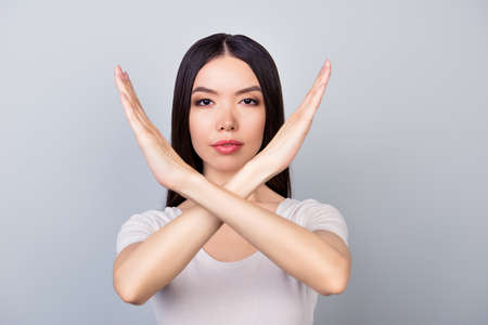 Foto de Close up of young brunette woman making stop gesture, forbidding something, standing in white outfit  on a grey background - Imagen libre de derechos