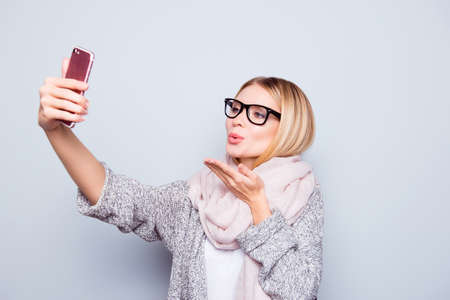 Foto de Beautiful charming lady in spectacles dressed in warm outfit is sending ari-kiss and taking selfie  on her cellphone. She is isolated on grey background - Imagen libre de derechos