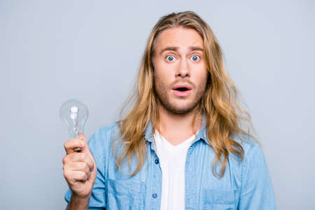 Foto de Wow! I even couldn't imagine that it is possible! Shocked and surprised young man with open mouth is holding a light bulb. He found out new fackts about some information - Imagen libre de derechos