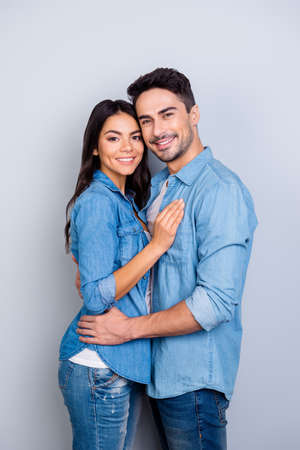 Foto de Together forever! Vertical photo of happy newlyweds dressed in jeans casual clothes, they are smiling, hugging and isolated on grey background - Imagen libre de derechos