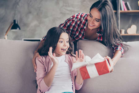 Photo pour Dreams come true on birthday! Here you are a present! Young charming mother in casual clothes is giving a red gift box to her surprised and cheerful little princess - image libre de droit