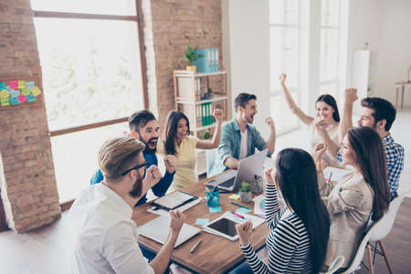 Photo for Close up of successful team of business partners with raised up hands in light modern workstation, celebrating the growth of the income - Royalty Free Image