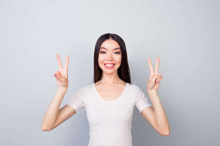 Foto de Portrait of glad, funny, smiling, toothy, beautiful girl showing with two hands v-sign, two peace symbols, standing over grey background - Imagen libre de derechos
