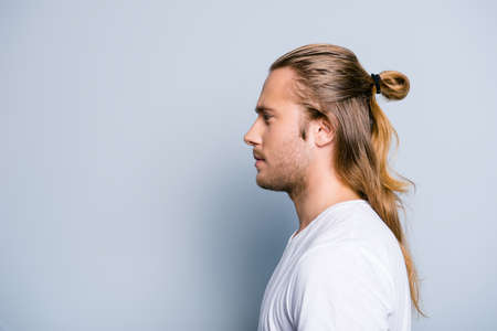 Photo pour Close up side view photo of serious confident young guy, he has hair bun, isolated on grey background - image libre de droit