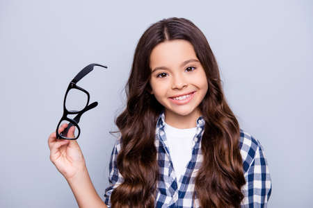 Photo pour Close up portrait of beautiful, charming, little girl taking out glasses and using lenses, smiling to the camera standing over grey background - image libre de droit