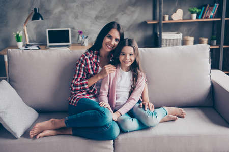 Photo pour So nice and admirable sweet tender family portrait! Charming cheerful mom and her cute kid are hugging and sitting on a sofa at home - image libre de droit