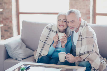 Photo pour It is almost winter, so cold outside, but so sweet time we spend together! Happy cheerful peaceful couple of pensioners are resting,  relaxing, hugging, drinking tea with closed eyes at the weekend - image libre de droit