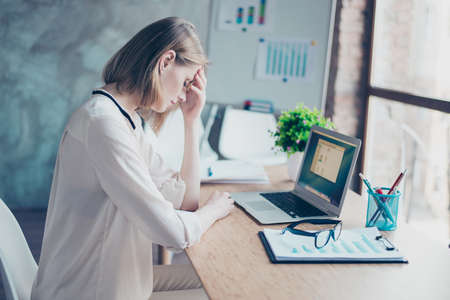 Photo pour Concept of getting a headache at work. Beautiful young smart secretary is sitting at the table, having a headache and touching her forehead - image libre de droit