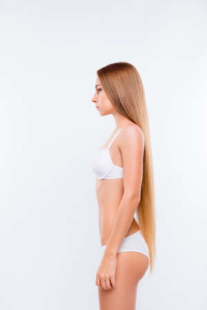 Photo for Vertical side view photo of young beautiful slim girl wearing white underwear, she has long smooth blonde hair, she is on a diet, isolated on white shadeless background - Royalty Free Image