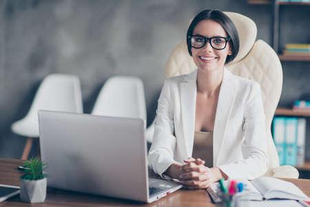 Foto de Portrait of confident smart successful beautiful businesswoman wearing white jacket, she is sitting in front on the computer at her workstation - Imagen libre de derechos
