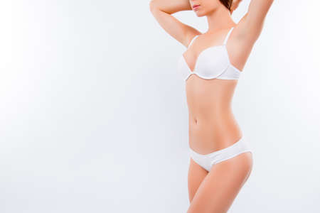 Foto de Concept of healthy lifestyle and nutrition, perfect skin and shape. Close up photo of ideal sexy woman's body wearing white brassiere and penties,  holding her hands, isolated on white background - Imagen libre de derechos