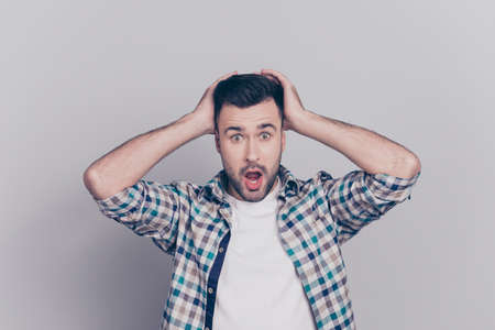 Photo for Portrait of surprised, shocked man with stubble and wide opened mouth and eyes in checkered shirt touching head with two hands isolated on grey background - Royalty Free Image