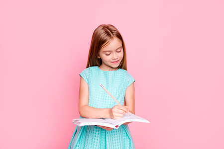 Foto de Lovely adorable charming little girl is looking down at the copybook in her hands and writing information there - Imagen libre de derechos