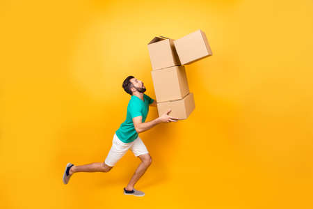 Foto de Funny nervous man is carrying his stuff in boxes to the recently bought flat. He is holding cardboard boxes and one is falling down - Imagen libre de derechos