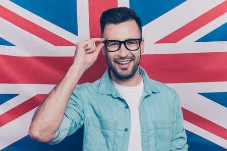 Photo pour English language learning concept-portrait of cheerful man with bristle holding his hand on glasses standing over English flag background - image libre de droit