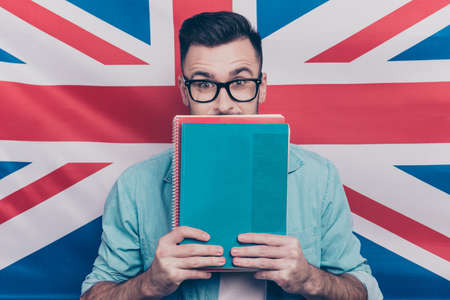 Photo for English language learning concept-portrait of excited man holding colorful copy books in hands closing half face with notebooks standing over English flag background - Royalty Free Image