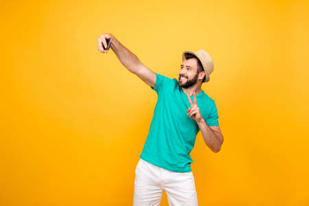 Foto de Hey what's up? Happy funky cheerful joyful man clothed in casual outfit taking a self portrait on his new smartphone and showing two fingers, copyspace - Imagen libre de derechos