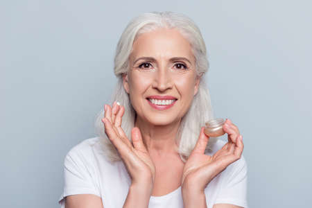 Foto de Close up portrait  of senior, attractive, pretty, nice,  woman with beaming smile holding, having, applying anti-aging, for dry skin cream, lotion over grey background - Imagen libre de derechos