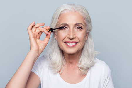 Photo for Nice, delighted, caucasian, charming, pretty, aged woman applying black mascara, dye eyelashes using tassel, making, doing professional make up over grey background - Royalty Free Image