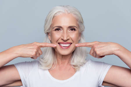 Foto de Concept of having strong healthy straight white teeth at old age. Close up portrait of happy with beaming smile female pensioner pointing on her perfect clear white teeth, isolated on gray background - Imagen libre de derechos