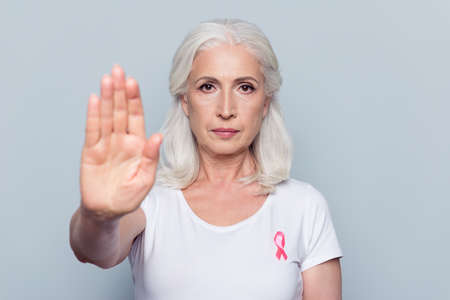Foto de Pretty, attractive, nice woman with Breast Cancer awareness pink ribbon on her white t-shirt, making stop sign with her hand, palm to the camera over grey background - Imagen libre de derechos