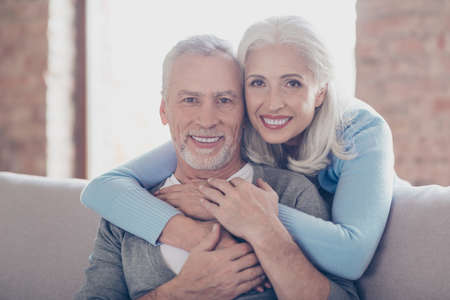 Foto de Close up portrait of two happy old married people, they are hugging and have perfect shiny white smiles - Imagen libre de derechos