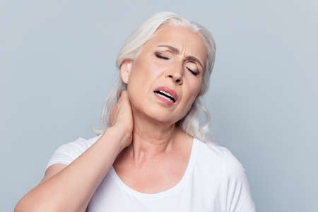 Foto de Aged, pretty, attractive, nice woman feeling exhausted, holding hand on neck, chilled, stretched out, suffering from pain with close eyes over grey background, health care concept - Imagen libre de derechos