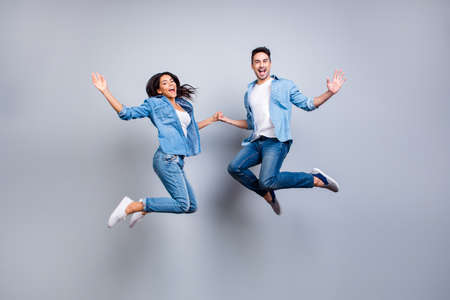 Photo for He vs She full length portrait of attractive, playful, cheerful, hispanic couple in casual outfit jumping with opened mouths over grey background - Royalty Free Image