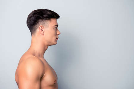 Photo pour Half-faced profile side view portrait of confident sexy shaven with modern hairstyle sporty guy with perfect smooth skin, isolated on grey background, copy space - image libre de droit