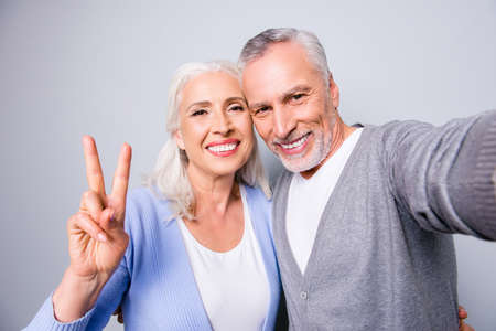 Foto de Happy sweet memories! Close up photo of senior couple showing two fingers and taking a selfie, isolated on grey background - Imagen libre de derechos