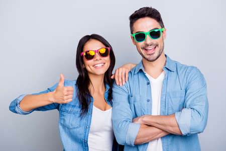 Photo for Attractive cool beautiful partners in summer glasses smiling to the camera, girl making thumb up sign, man with crossed hands over grey background - Royalty Free Image
