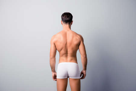 Photo for Back view photo of handsome confident guy with strong back and shoulders, wearing white underpants, isolated on grey background, copyspace - Royalty Free Image