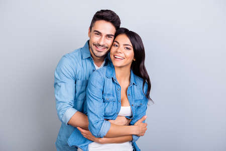 Foto de Portrait of cheerful lovely cute couple with beaming smiles hugging and looking at camera over grey background - Imagen libre de derechos