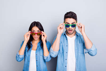 Photo pour Oh my God! Shocked partners  with wide opened mouths and eyes peering out summer glasses  over grey background - image libre de droit