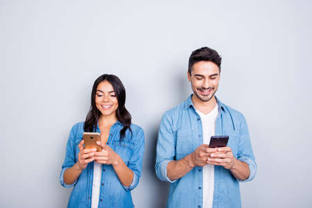 Foto de attractive, cheerful, smiling lovers in casual outfit, jeans shirts  having smart phones in hands, looking at screen, texting with each other, using 5g internet, standing over grey background - Imagen libre de derechos