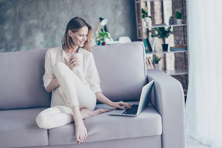 Photo pour Beautiful smiling blonde woman sitting on couch using wi fi internet on her laptop for  online shopping  holding cup of tea - image libre de droit