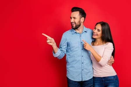 Photo pour Portrait of smiling, embracing, excited, attractive couple pointing to copy space with forefinger over red background, having date - image libre de droit