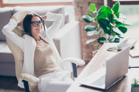 Photo for Nice, independent, cute woman in white suit, formal wear, glasses sitting on chair at her desk in office, holding arms behind the head with close eyes, thinking about holidays, vacation - Royalty Free Image