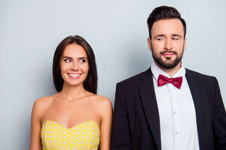 Photo pour Cute, attractive, beautiful, playful, stylish, funny family, shy couple in elegant wear standing over grey background, shoulder to shoulder, wife and husband looking to each other with eyes, he vs she - image libre de droit