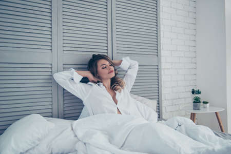 Photo pour Rest, sleeping, comfort and people concept - young woman stretching in bed in light room at home bedroom, hands behind the head, dreaming about breakfast in bed - image libre de droit