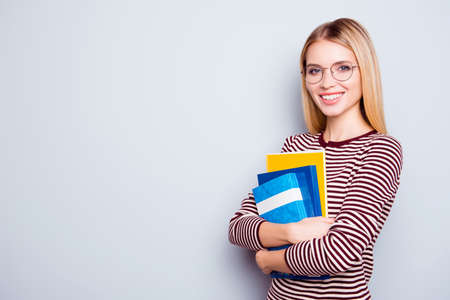 Photo for Cute clever confident beautiful young woman wearing striped sweater and round glasses is holding a pile of book in hands, isolated on grey background - Royalty Free Image