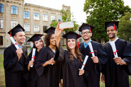 Photo for Memories of six international cheerful graduates, posing for shot, attractive brunette lady is taking, wearing gowns and mortar boards, outside on a summer day, so excited and gathered - Royalty Free Image