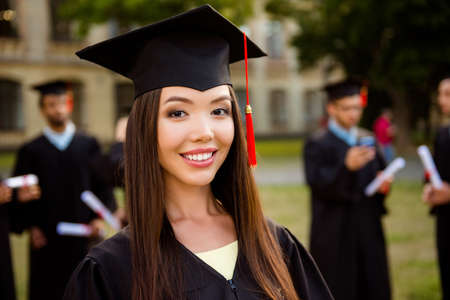 Foto de Happy cute chinese brunette girl is smiling, blurred class mates with diplomas behind. She is in a black mortar board, with red tassel, in gown, brown hair, toothy white smile grin, so excited - Imagen libre de derechos
