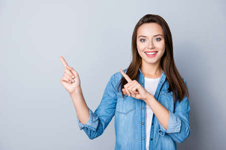 Photo pour Advertisement concept. Positive, pretty, caucasion woman with beaming smile in jeans shirt  on grey background  is pointing with her two index finger and looking on empty copy space - image libre de droit