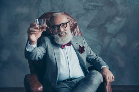 Photo pour Portrait of bearded, lucky, old rich man in formal wear with bow tie and pocket square, sitting on chair, holding, raise glass with whiskey,  crypto-currency, shares, stock - image libre de droit