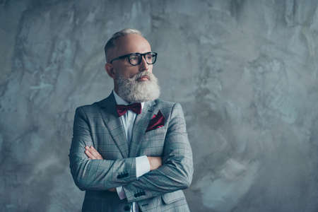 Photo pour Portrait of modern luxurious trendy wealthy intelligent dreamy pensive stylish authoritative clever man wearing checkered grey jacket chic maroon bow-tie imagine smth, isolated on concrete background - image libre de droit